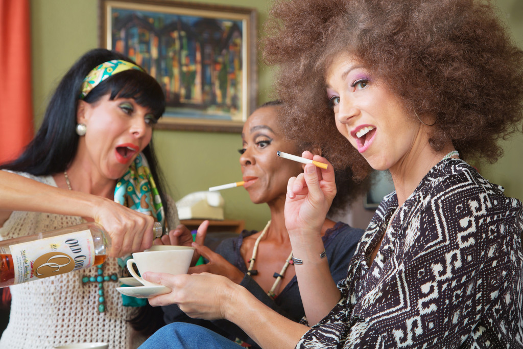 Laughing women smoking cigarettes and drinking alcohol